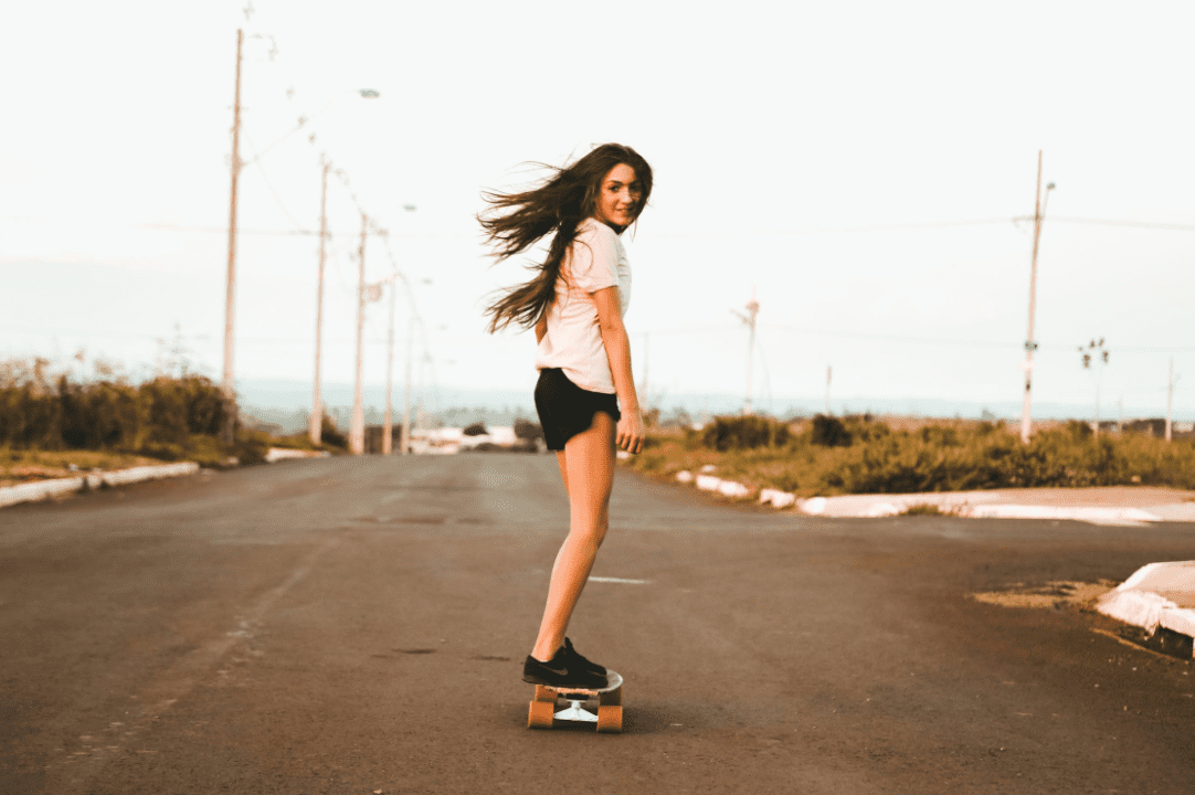 woman wearing white tees and black shorts riding a long board in the road