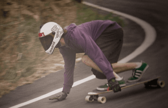 Man in purple and wearing a helmet while riding a madrid longbord