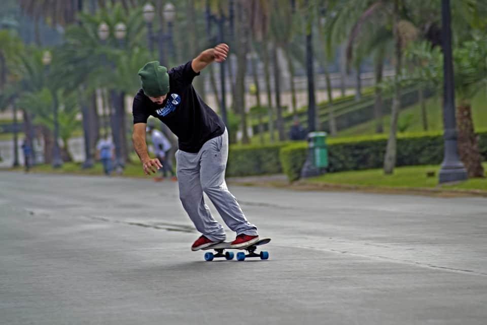 man wearing bonnet riding a longboard