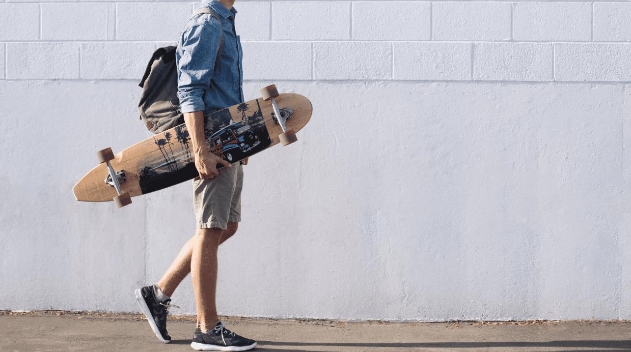 Man in denim shirt carrying his Arbor Longboard