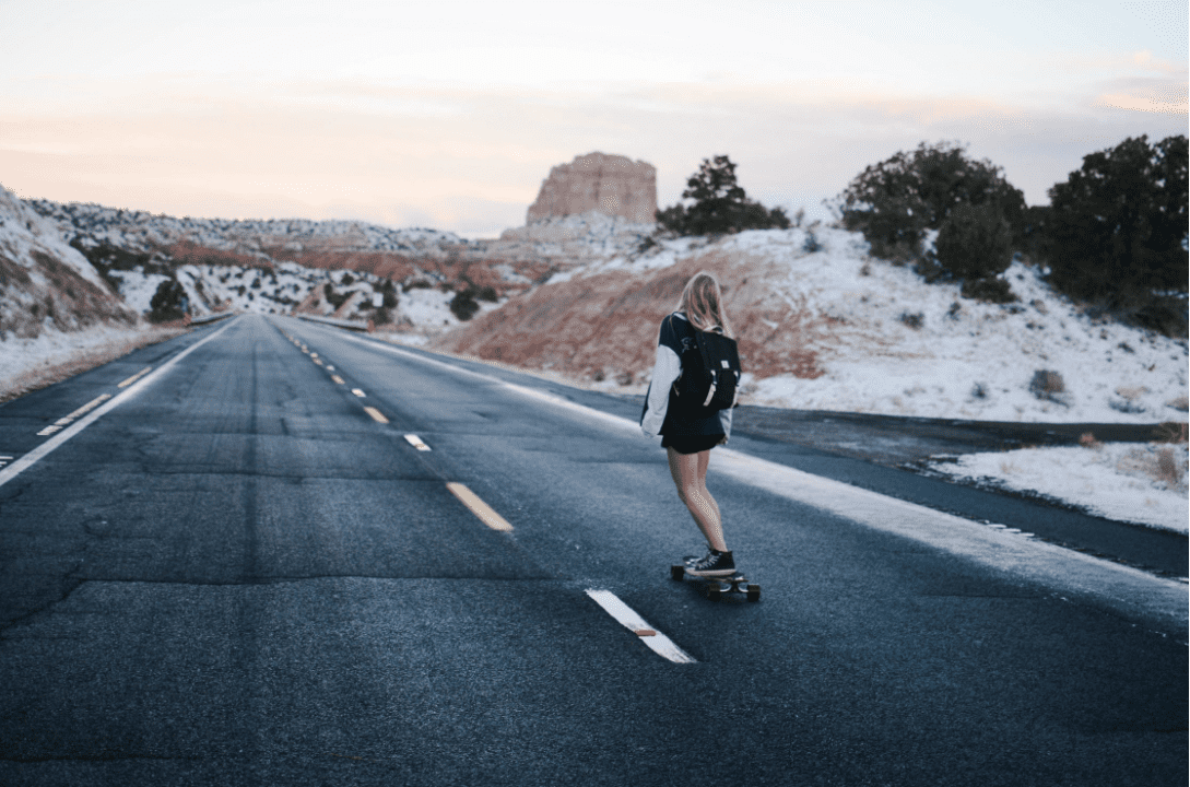Woman in the road riding her pantheon longboards