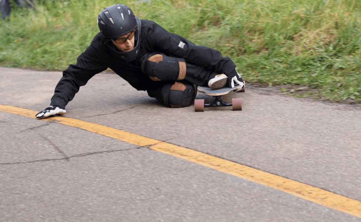 Man wearing black skateboard gear maneuvering his zumiez longboard on the road