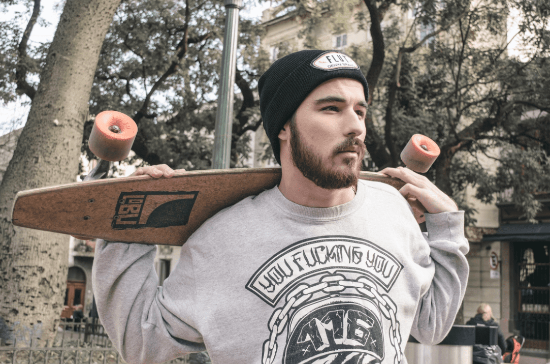 Arbor Longboard on the shoulder of a bearded man