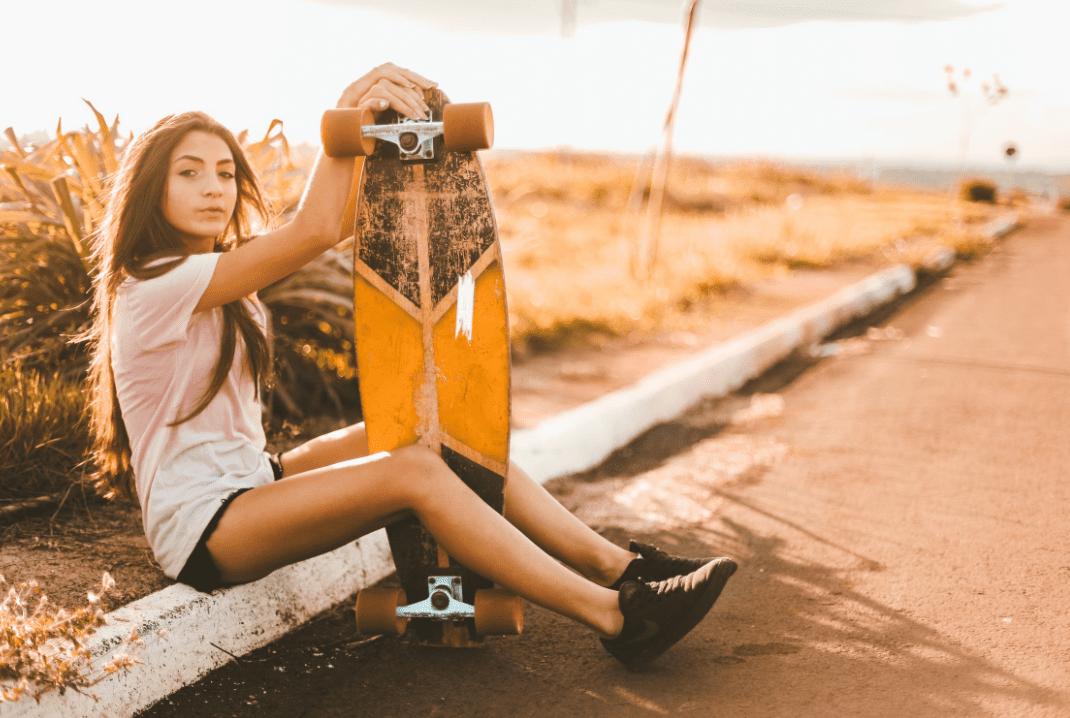 Woman on the road while holding her Arbor Longboard