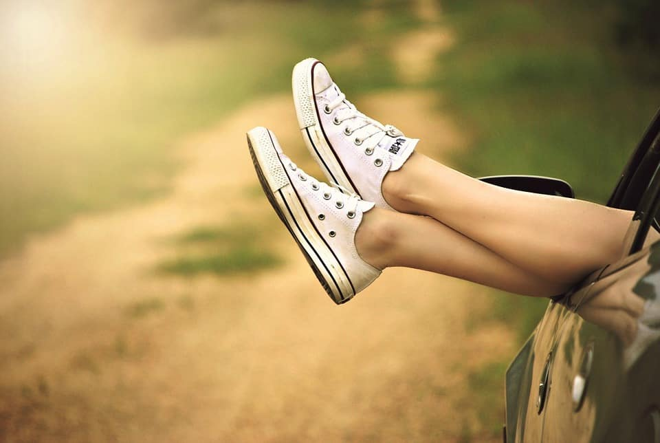 person wearing white converse shoes