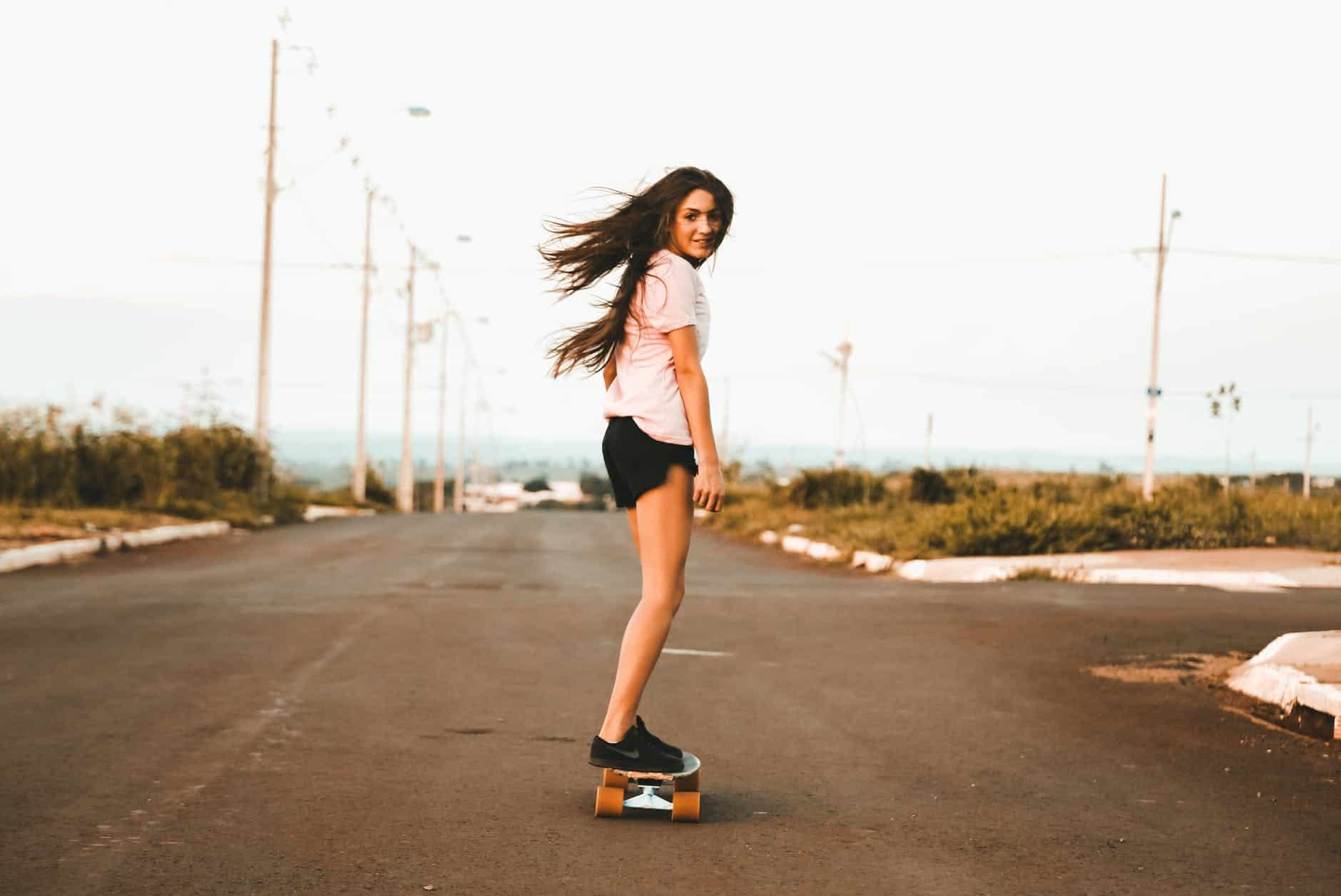 girl riding a revive skateboard on the road